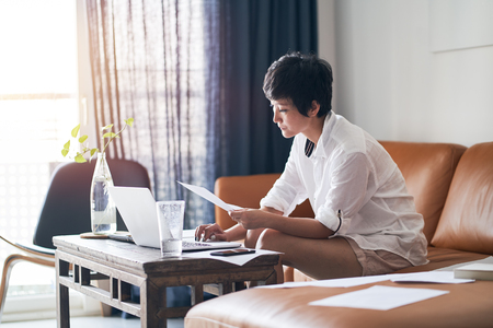 Asian self employed woman sitting on couch thinking & working on laptop at home Stock fotó