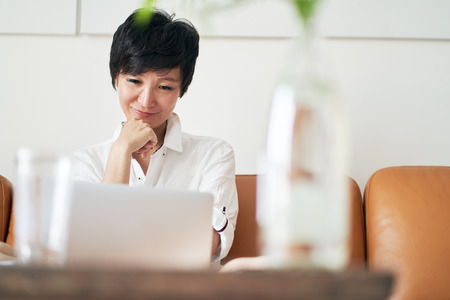 Asian self-employed woman smiling while working on laptop at home Stock fotó