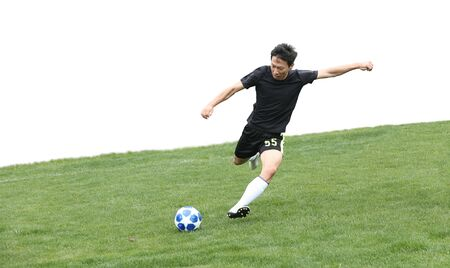 Asian soccer player kicking ball