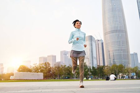 Portrait of Asian beauty jogging in city park at sunset Stock Photo - 133934493