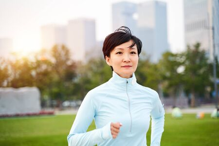 Portrait of Asian beauty jogging in city park at sunset