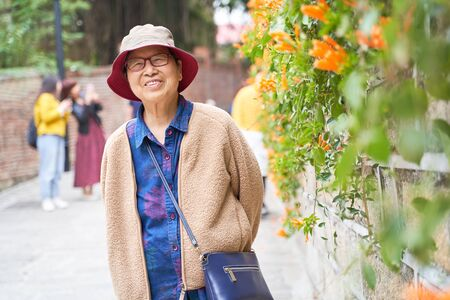 portrait of senior Asian traveler standing and similing beside flowers