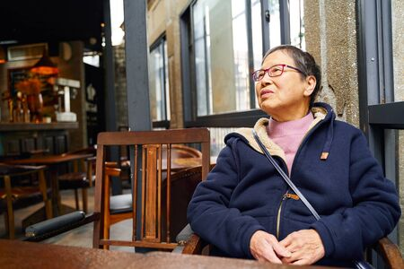 portrait of senior Asian woman sitting alone in cafe