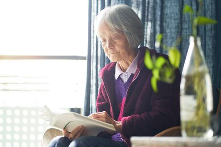 senior Asian woman reading a book at home enjoying retirement Stock Photo