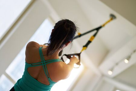low angle rear view of asian woman doing TRX suspension exercise indoors