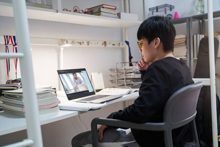 Asian kid studying at home on laptop wearing computer glasses during covid-19
