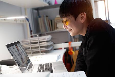 Asian kid studying at home on laptop wearing computer glasses during covid-19 Stock Photo - 145059940