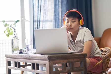 Asian teenage boy studying at home wearing headset & getting bored Stock Photo