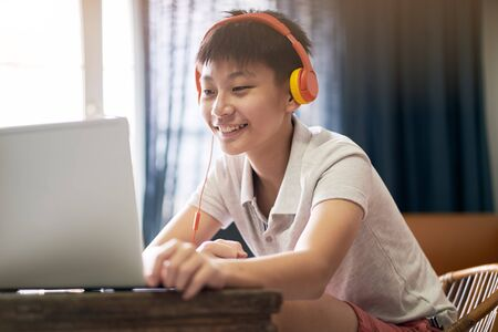 Asian teenage boy studying at home during pandemic wearing headset and smiling