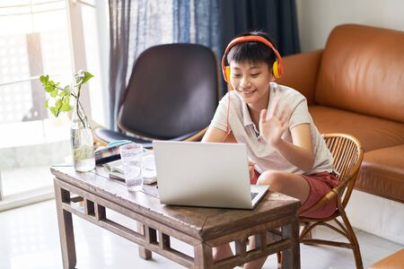 Asian teenage boy studying at home wearing headset, smiling & saying hello