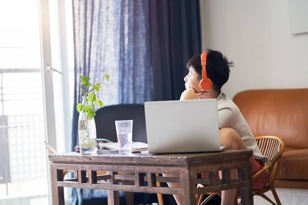 Asian teenage boy studying at home getting tired and looking out of window Stock Photo
