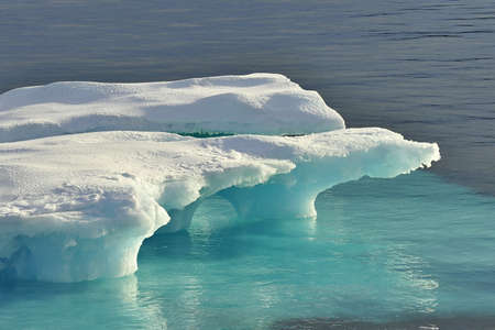Global warming. Icebergs and mountains in the ocean.