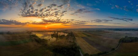 A beautiful morning starts with a dramatic sunrise over a lake. Banco de Imagens - 130814219