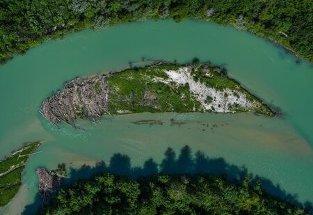 A lonely island in the Isar river in vertical view from a drone