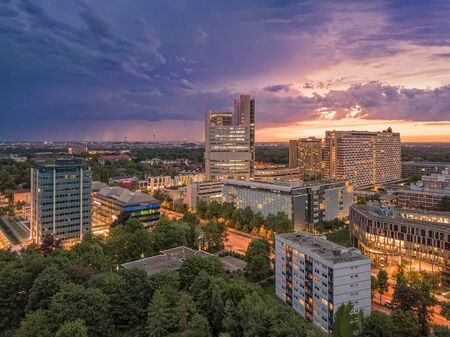 Munich skyline with office buildings at sunset, light in the streets