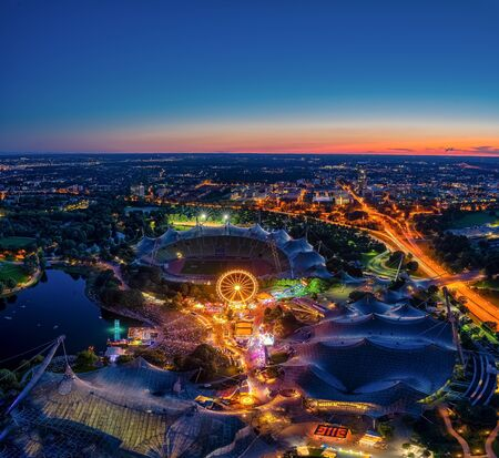 Amazing aerial view at Munichs Olympic park at night with many colored lights from a festival.