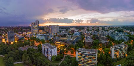 Munich from above, a panoramic droneshot in the colorful evening with office bulidings in a working discrict. Фото со стока