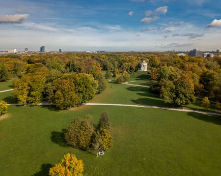 A droneshot at autumn colors at the Englischer Garten of Munich, beautiful day.