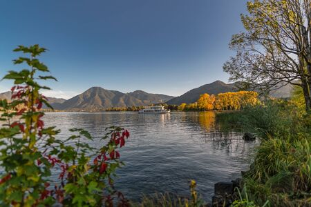 A beautiful lake with autumn colored plants with a mountain in background.
