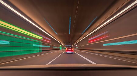 Fast driving car through a tunnel with blurry light effects, a urban race scene with leading lines and symmetry structure.