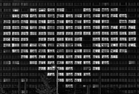 Heart shape illuminated windows of a building as a gesture for people who support others like now in hard corona virus times symbolically in black in white.