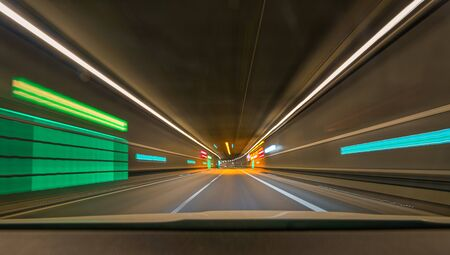 Fast driving with my car through a tunnel with leading lines and lights.