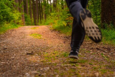 Jogging feet of a running man from low perspective in a green forest at springtime. Dynamic photo of a popular human activity to increase somebodys fitness level.