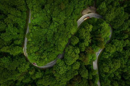 Wonderful green forest with a curvy road and cars from a top view drone shot, aerial of an s curve background which implicates fun of driving or take a trip through the nature.