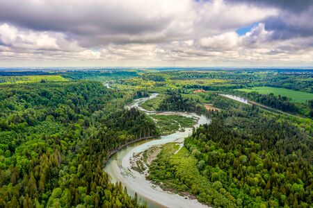 Aerial view at the curvy Isar river at a sunny but cloudy day from nearly 100m from above in southern bavaria, germany. Beautiful nature at springtime. Foto de archivo
