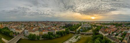 Munich from above at springtime, panoramic view over the bavarian city at sunrise. Overview over many houses including the popular Frauenkirche. 写真素材
