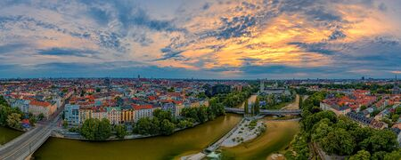 Dramatic sky at sunrise over Munich as panoramic aerial with a wonderful wide view over the bavarian capital city. View at the Frauenkirche in background. 写真素材