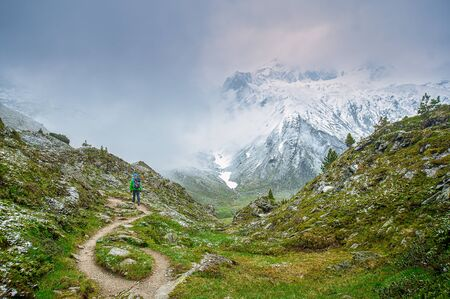 Foggy view at a mountain scenery in the austrian alps. A hiker from behind is watching at the snowy peak far away through the fog 写真素材
