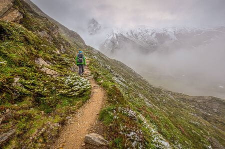 A hiker is walking up a hillside with a beautiful mounitain in the foggy background 写真素材