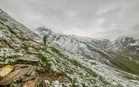 A hiker is walking up a snow covered hillside with a beautiful mounitain in the foggy background
