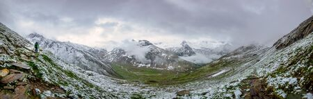 Panoramic photo of a hiker who is walking up a snow covered hillside with a beautiful mounitain in the foggy background