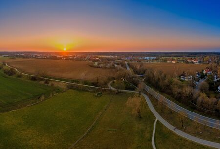 Beautiful sunset behind a bavarian village with a field in the foreground.
