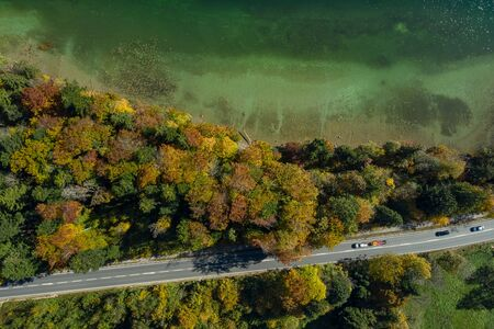Top view drone shot of a lake with a colorful forest at autumn and a street in the lower side of the photo. 写真素材