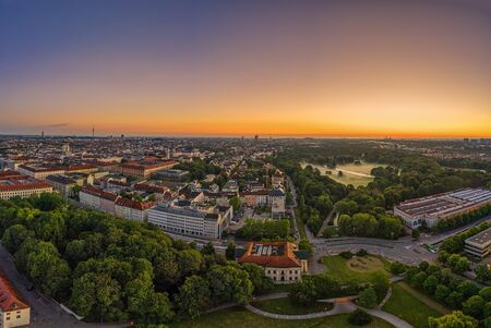 Wide view over Munich at the morning, where the popular green park called Englischer Garten is covered by fog. Panoramic sunrise view from a drone.