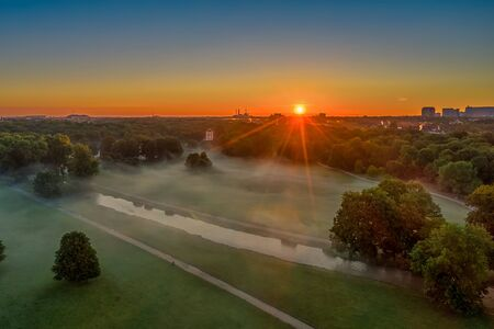 The Englischer Garten in Munich in the early morning. Sun is rising and the foy is ruling in the green park at a beautiful spring day, germany.
