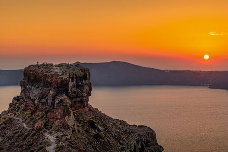 View at the rock Skaros of Santorini, Greece. The sun is going down over the sea, and the rock is popular for climbing ob it, to watch the impressive scenery.