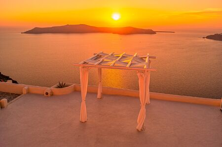 Sunset view from Santorin village Imerovigli over the caldera in a wonderful orange colored atmosphere in summer