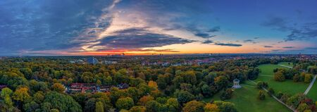 Impressive sunrise over Munich - drone shot over the Englischer Garten of the bavarian capital as great background pano