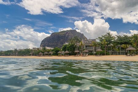 Paradise view at Mauritius. View from the ocean water to the popular rock called Le Morne Brabant with sandy beach at a warm summer day.