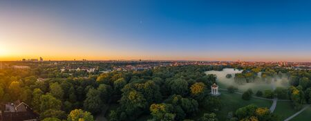 Fog in Munich. Misty aerial view in the popular Englischer Garten and a total view ovewr the skyline at sunrise.