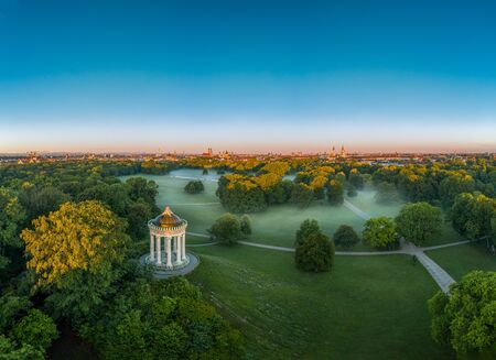 Wonderful aerial view over the Englischer Garten of the bavarian capital Munich at the early morning with fog in the green park. 写真素材