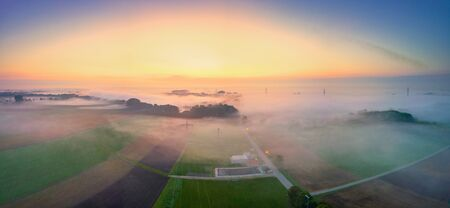 Foggy view over a field at sunrise and electricity pylon
