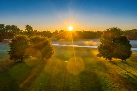 Sunny morning in the park, aerial footage in the Englischer Garten of Munich, sunbeams are shining through a groupt of trees. 写真素材