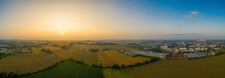 Drone footage - sunrise view over fields and a nearby situated business district, covered by the fog of the early wet morning. 写真素材