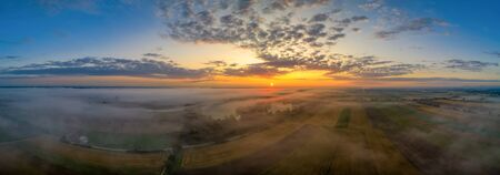 Beautiful morning with upraising fog over a panoramic field view at sunrise pure nature.