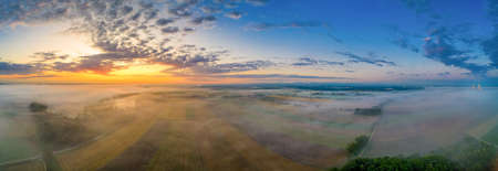 Sunrise glow over a foggy field in bavaria, germany at a wonderful morning in summer.